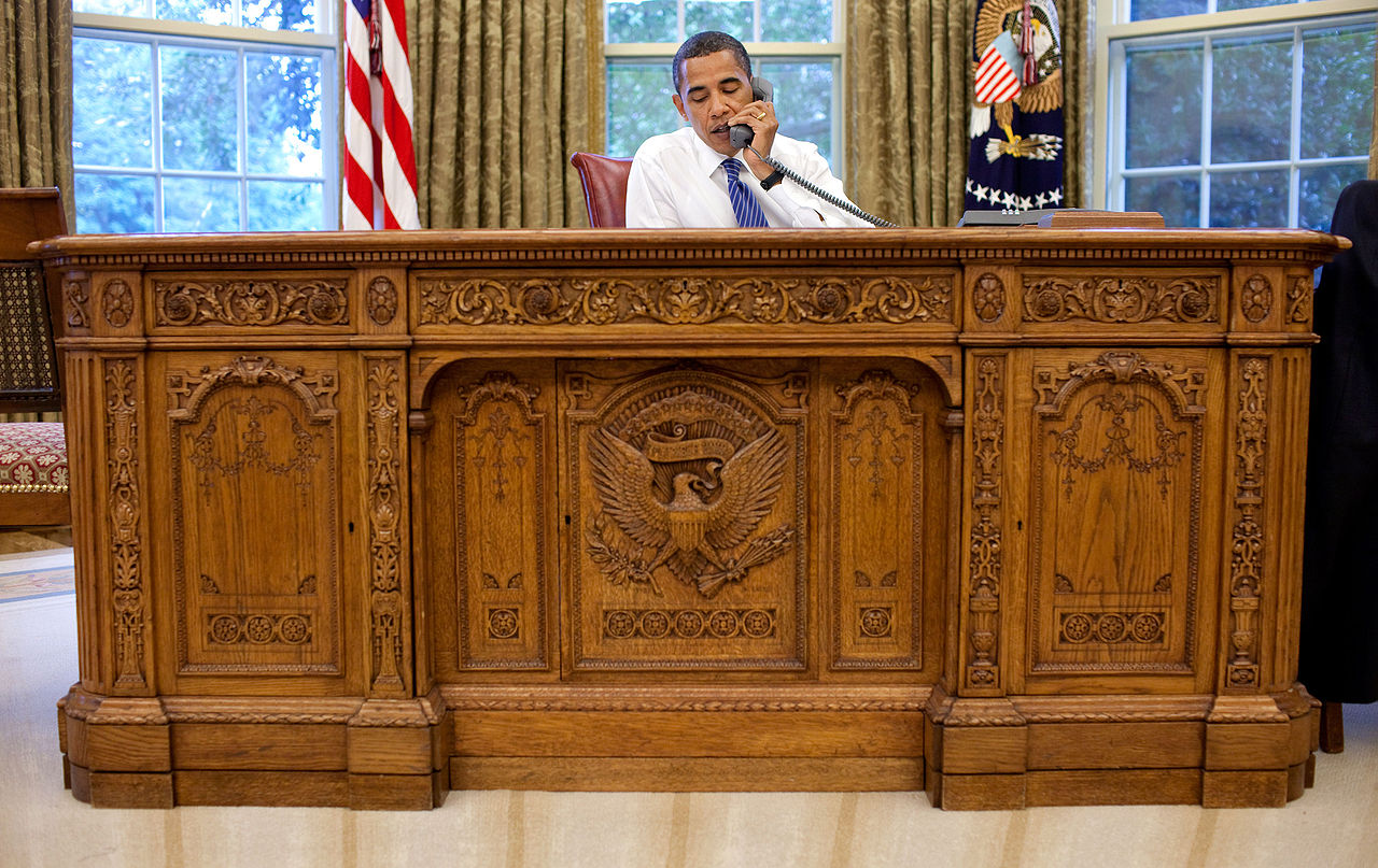 1280px-Barack_Obama_sitting_at_the_Resolute_desk_2009.jpg